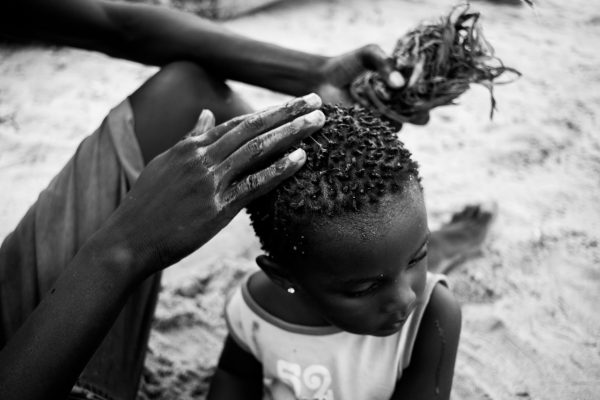 Wasta, locking the hair of his friend's daughter. Using a sap from the bark of a Mkone(Grewia) tree. Indigenous locals also use the sap as a detergent. Biko Wesa, Kenya. 2018.